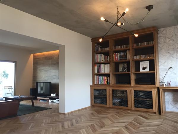 【LDK】LDKの床材はオークの無垢材をヘリンボーン様式で張っています。リビングダイニングの天井・壁は珪藻土。パターンはランダムです。オーディオを置く壁面はアクセントに石目のパネルを張っています。キッチンの天井はモルタル仕上げです。照明をインダストリアルなものを使用し雰囲気を変えています。またLDKには造作で飾り棚と本棚・書斎を拵えています